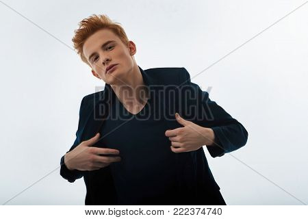 Hunk. Attractive unsmiling red-haired young man putting his jacket on and staring and having a modern haircut