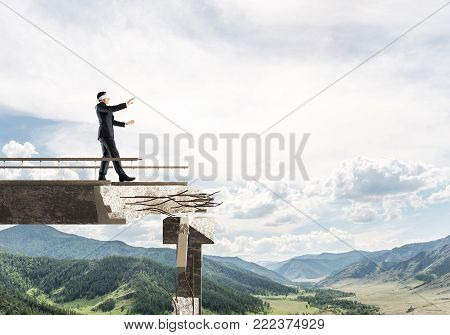 Businessman walking blindfolded on concrete bridge with huge gap as symbol of hidden threats and risks. Skyscape and nature view on background. 3D rendering. poster