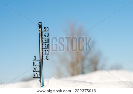 Weather forecast. Thermometer on snow show low temperature. Blue sky. Meteorology concept