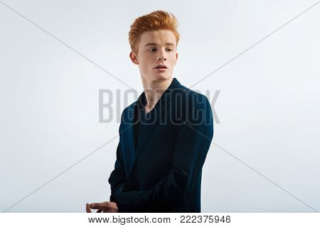 Thinking. Attractive unsmiling young red-headed man buttoning up his sleeve and having a serious expression on his face and looking over his shoulder