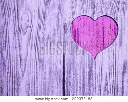 Pink heart carved in a wooden board. Background. Postcard, valentine