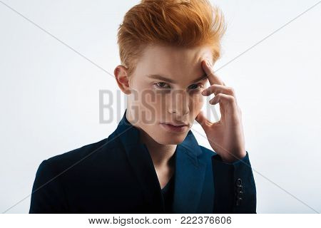 Thinking. Attractive meditative red-haired young man wearing a black jacket and touching his forehead and thinking