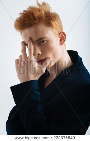Modern hairstyle. Good-looking unsmiling red-haired young man wearing a black jacket and touching his forehead and staring