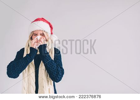 studio picture from a young woman with handkerchief. Sick girl isolated has runny nose. Female model makes a cure for the common cold.
