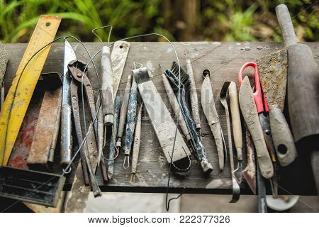Set of dirty craft sculpting tools on wooden table