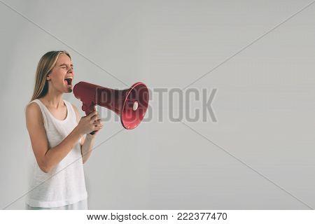 Portrait of young women shouting using megaphone over background Girl in white shirt, studio shot