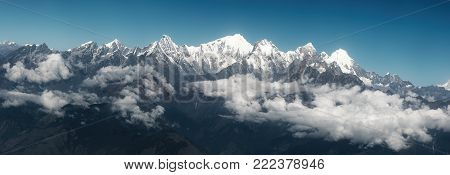 Panoramic view of snow mountains range landscape with blue sky