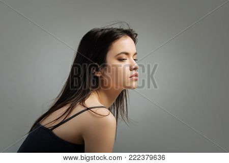 Preoccupied. Beautiful serious long-haired young woman thinking and looking in the distance and wearing a top