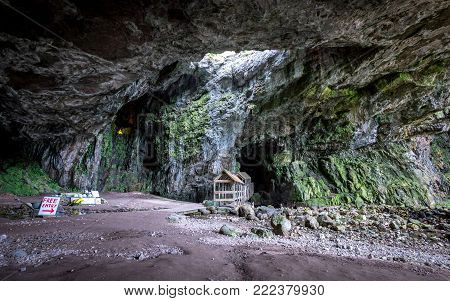 Smoo Cave outer chamber, Durness, Scotland. The outer chamber of Smoo Cave near Durness on the northern coast of Scotland.  The main entrance is to the right while the covered walkway leads to the second inner cave.