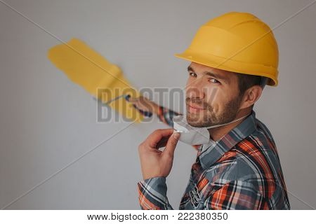 The builder works at the construction site and measures the ceiling. A worker in an orange helmet and a paint roller paints the wall