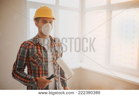 The builder works at the construction site and measures the ceiling. A worker in an yellow helmet and a paint roller paints the wall
