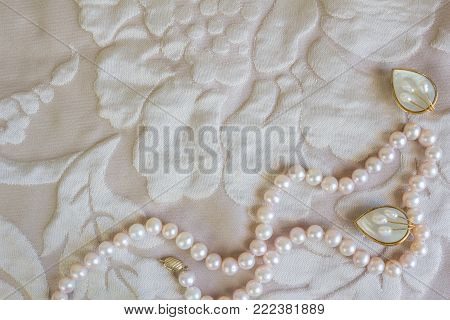 Pearl necklace and mother of pearl ear rings on pale rose satin texture background / Pink pearl string and two white mother of pearl ear studs
