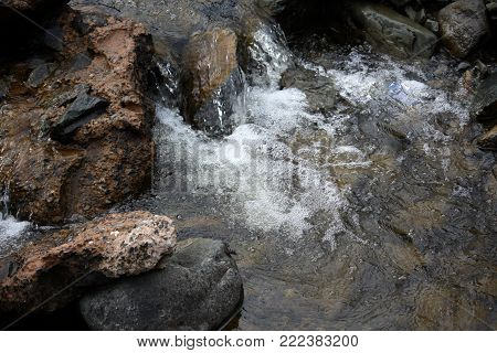 The water bubbles into a small pool from a mountain stream