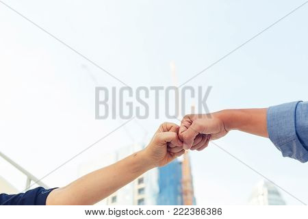 business man and woman fist bumping for celebration and successful concept on constuction background