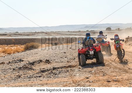 Merzouga, Morocco - February 25, 2016: Two Riders On Quad Atvs Wait Beside A Riderless Motorbike On