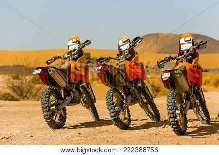 Merzouga, Morocco - February 24, 2016: Three orange motorbikes lined up ready to go on a Sahara desert adventure. They sit under a bright blue sky on a sunny day. A range of hills can be seen in the distance