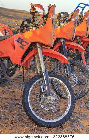 Merzouga, Morocco - February 25, 2016: Several Orange Motorbikes Lined Up Ready To Go On A Sahara De