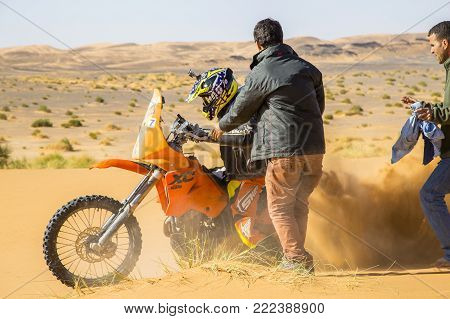 Merzouga, Morocco - February 25, 2016: A Motorbike Rider Churns Up Sand As He Tries To Get His Orang