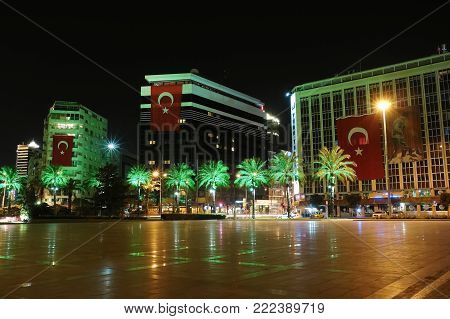 Izmir, Turkey - April 22, 2012: Night view of the square with modern buildings and palms in the city of Izmir, Turkey.