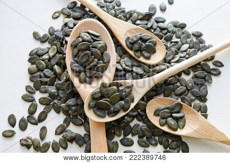 fresh dark green Styrian pumpkin seeds in wooden spoons over white table background