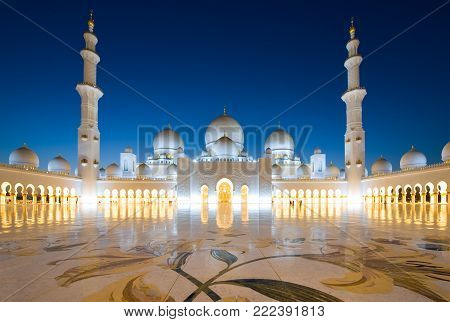 ABU DHABI, UNITED ARAB EMIRATES - DEC 31, 2017: Exterior of the Sheikh Zayed Mosque in Abu Dhabi in twilight. It is the largest mosque in the country.