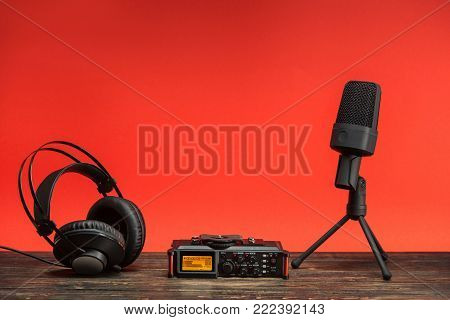 equipment for field audio recording on red background. Usb microphone, recorder and headphones
