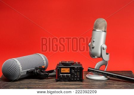 equipment for field audio recording on red background. Shotgun microphone, usb microphone, recorder and windshield