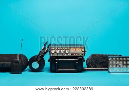 equipment for field audio recording on blue background. Windshield, shotgun microphone, radio system, portable case, mixer and headphones