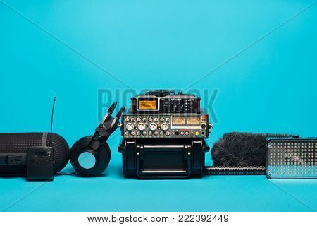 equipment for field audio recording on blue background. Windshield, shotgun microphone, radio system,  recorder, portable case, mixer and headphones