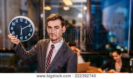 Portrait of young businessman standing and holding alarm clock.smiling working on modern loft office at night sitting at office with team staff and working late overtime.