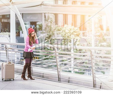 Woman traveler looking at travel map in airport walkway with travel bag or luggage.. Concept of woman travel,