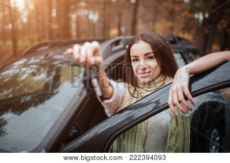 Woman holding car keys. Close up Hand. Woman holding car keys. Close up Hand. Autumn concept. Autumn forest journey by car