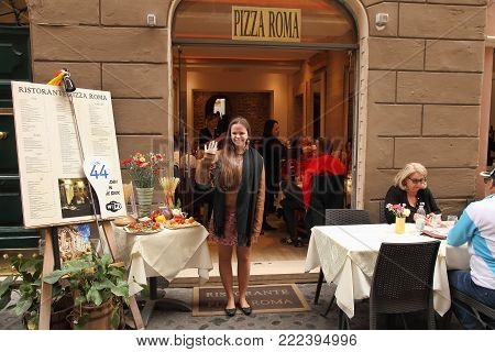 Rome, Italy - APRIl 9, 2017 : A smiling employee of the restaurant welcomes visitors at the entrance.