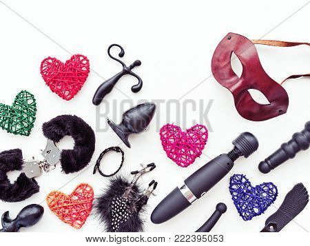 Black sex toys, brown leather venetian mask and colored figures of hearts from rattan are on a light background. Image for sex shop advertising (discounts, promo, banner, marketing)