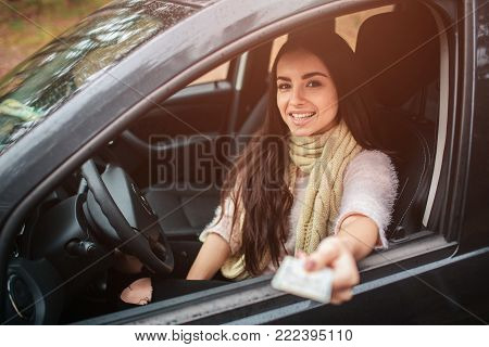 Woman showing driving license. Close up Hand. Autumn concept. Autumn forest journey by car.