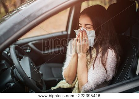 young woman with handkerchief. Sick girl has runny nose. female model makes a cure for the common cold in the car.