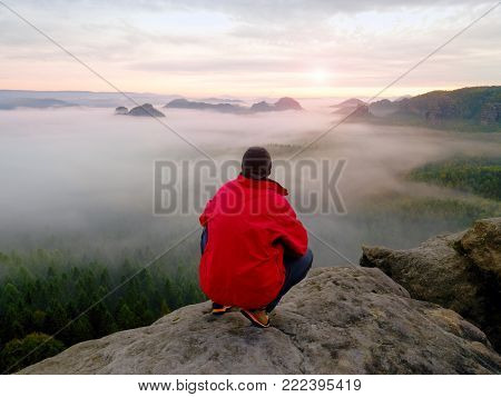 Enjoy life. Man in black trousers, jacket and dark cap sit on cliff's edge and looking to misty horizoon