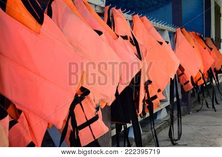 Hanging orange life jackets - selective focus