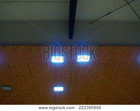 Wooden ceiling with lighting panels. Fluorescent lamps on the modern ceiling. Luminous ceiling of square tiles.