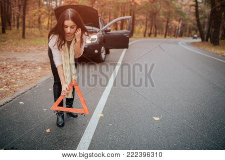 Auto assistance and insurance, troubles while traveling concept. Broken car and auto triangle on road, woman waiting for help.