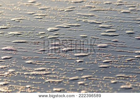 Sea foam. Abstract nature background image of bubbles in residual surf water on a sandy beach. Wet surface of sand.