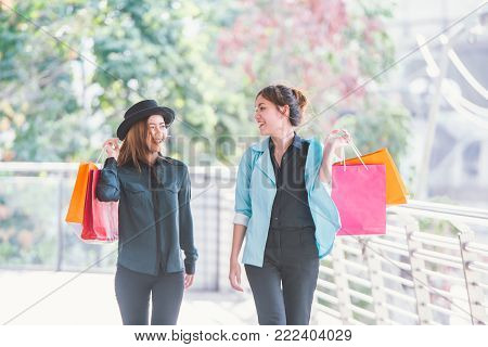 sale, consumerism and people concept - happy young women looking into shopping bags at shop in city.