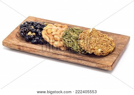 Korean traditional sweet snacks with peanuts, pumpkin seeds, black soybeans and chinese buckwheat on a wooden plate, isolated