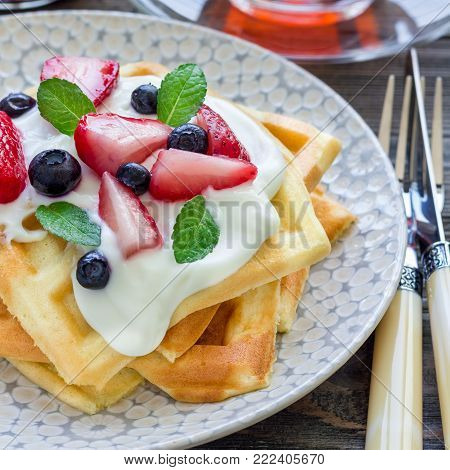 Homemade belgian waffles with yogurt, strawberry and blueberry, breakfast time, square format