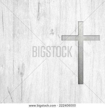 White old christian religion symbol cross shape as sign of belief on a grungy wood textured with copy space.
