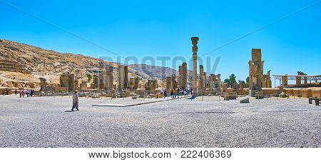 PERSEPOLIS, IRAN - OCTOBER 13, 2017: Panorama of stone Persepolis palace complex, the ruins of Hundred Columns Hall located at the foot of Rahmet Mount, on October 13 in Persepolis.
