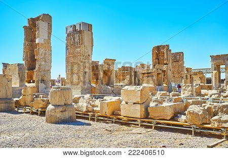 Remains of Hundred Columns Hall with complex relief on stone gates, ruined pillars and statues, Persepolis, Iran.
