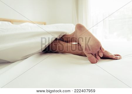 Barefoot of human on bed in morning. Single and Working people concept. Lazy day and Happiness home theme.