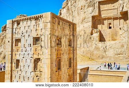 NAQSH-E RUSTAM, IRAN - OCTOBER 13, 2017: The rectangular Ka'ba-ye Zartosht tower with mausoleum of Darius II on the background, Naqsh-e Rustam Necropolis, on October 13 in Naqsh-e Rustam.