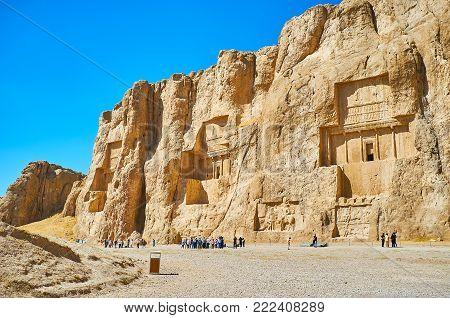 NAQSH-E RUSTAM, IRAN - OCTOBER 13, 2017: Naqsh-e Rustam Necropolis is the notable architectural ensemble of the ancent tombs, cut in rocky cliff, on October 13 in Naqsh-e Rustam.